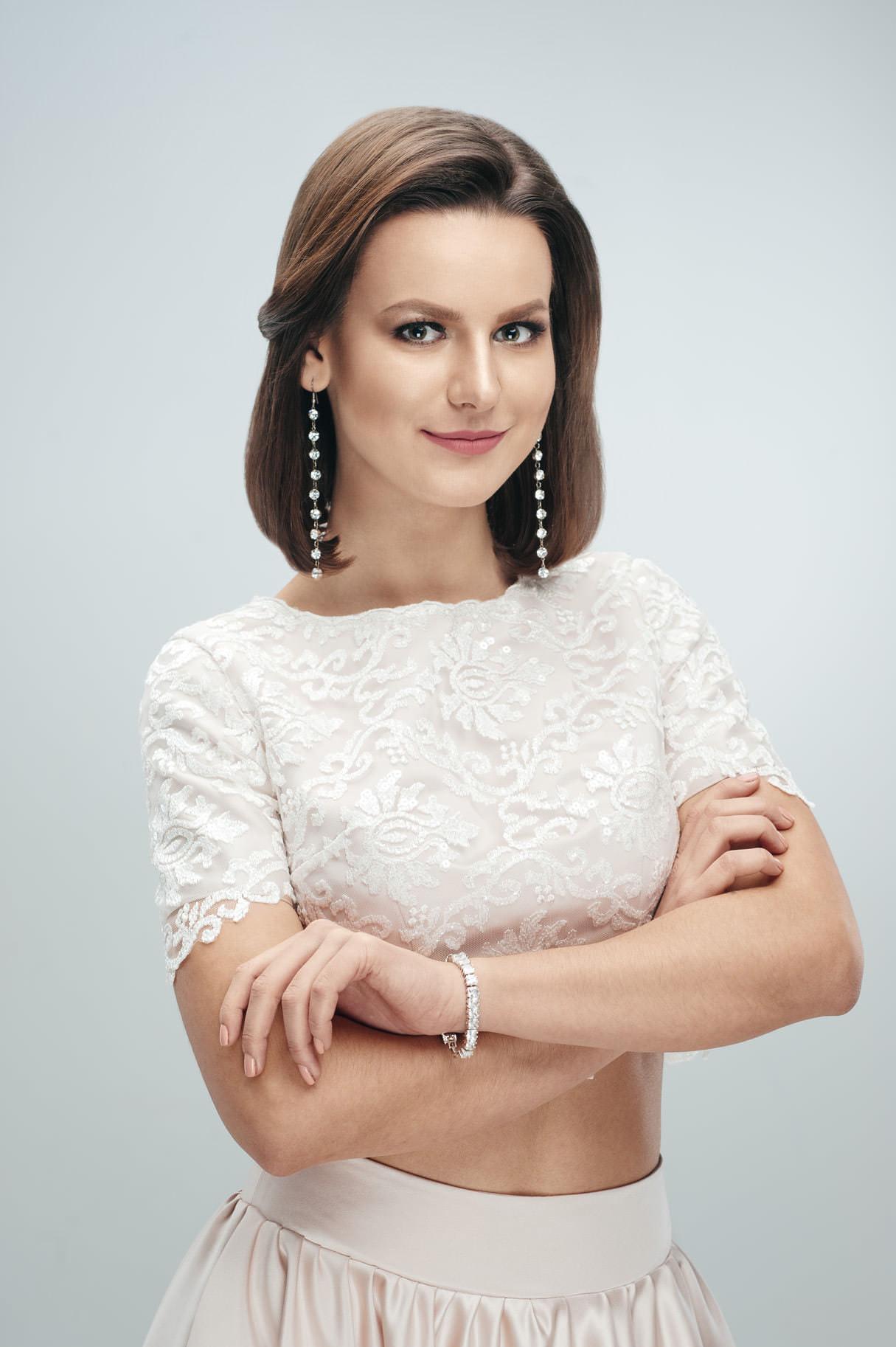 Деловой портрет женщины с украшениями и макияжем на светлом фоне, фотосессия в портретной студии Минска