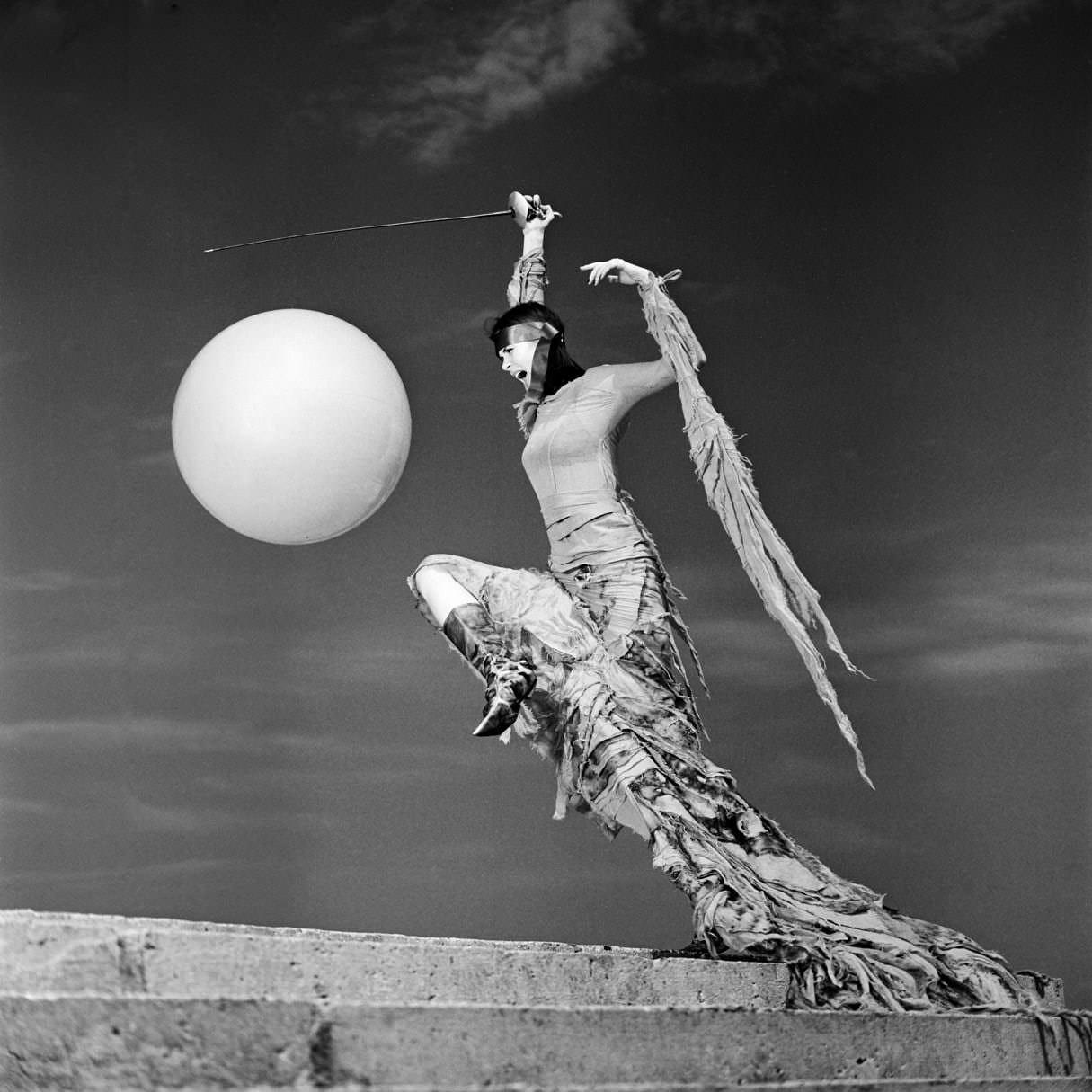 Черно-белая портретная фотография девушки в стильном платье со шпагой на фоне неба с шаром