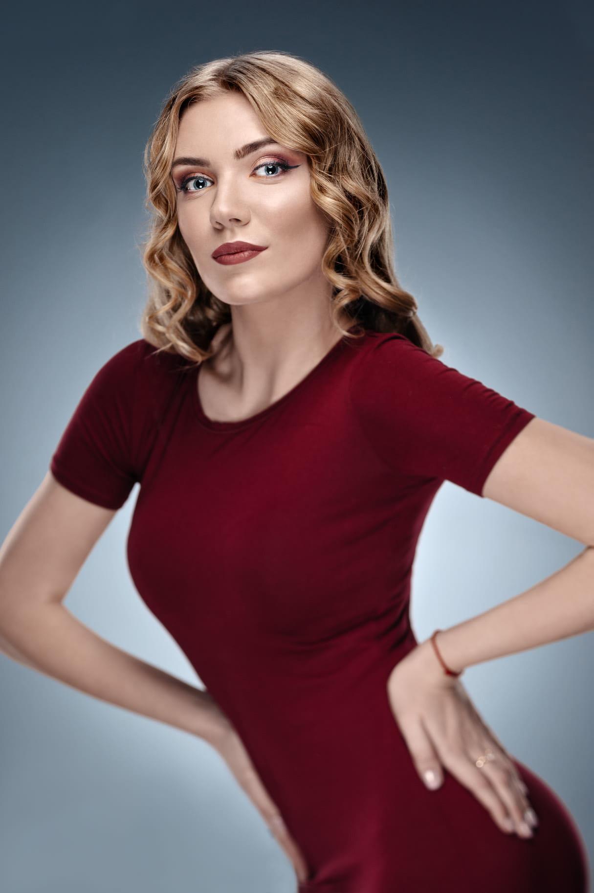 Художественный женский портрет в условиях фотостудии, фото девушки с макияжем в бордовом платье на голубом фоне