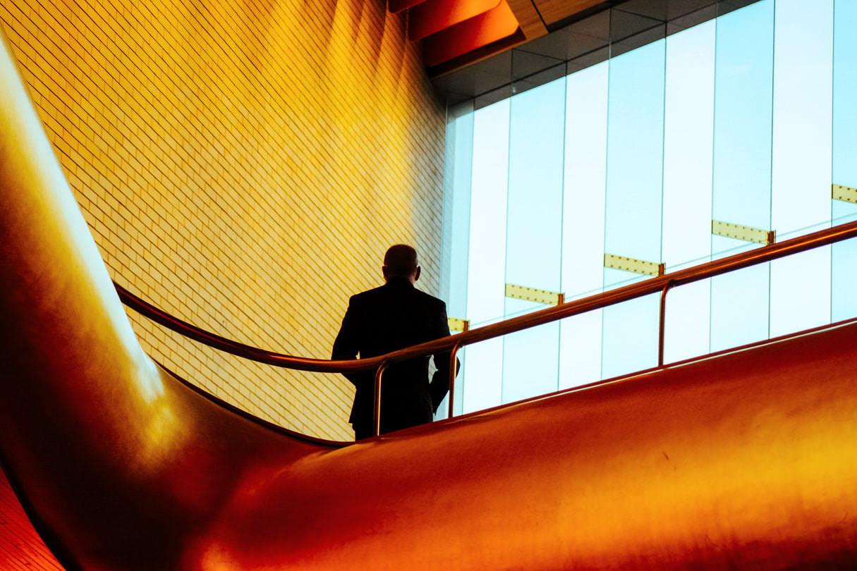 Деловая фотография сотрудника в интерьере компании, портрет мужчины со спины на фоне окна